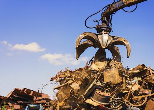 Ręka dźwigu wykonująca skup złomu na śmietnisku